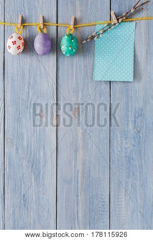 Handmade easter card and garland with painted eggs on wood background. Colorful holiday decoration on rustic table top view
