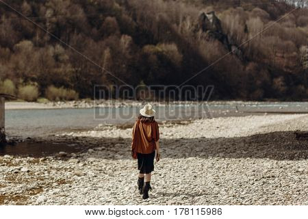 Stylish Boho Traveler Woman In Hat Back View, Fringe Poncho Posing Near Water River Beach In Mountai