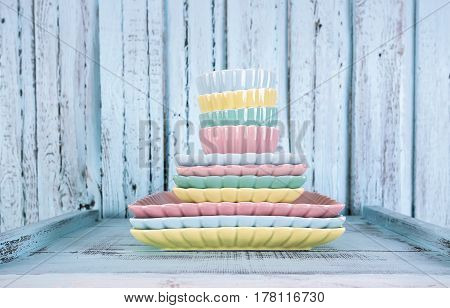 Pile plates on pastel color on blue wooden background