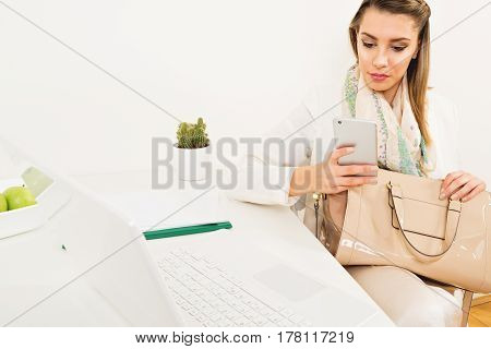 Young businesswoman at her office using smart phone. Fashionable modern female boss at work. Copy space, bright, contemporary, stylish.