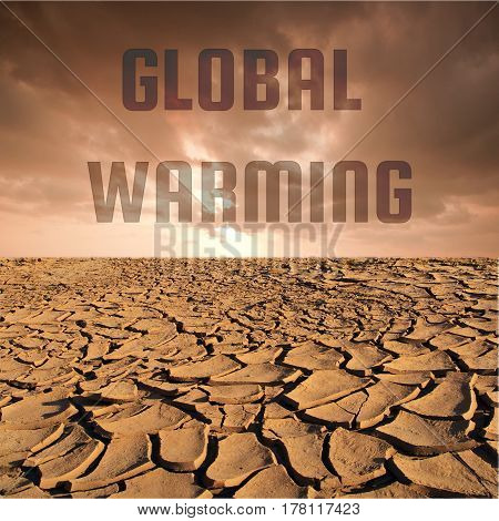 Global warming word on Cracked dry land without water and red sky background for Global warming concept
