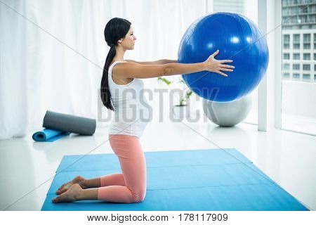Pregnant woman exercising with exercise ball at home