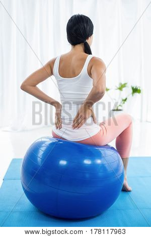 Pregnant woman exercising while sitting on exercise ball at home