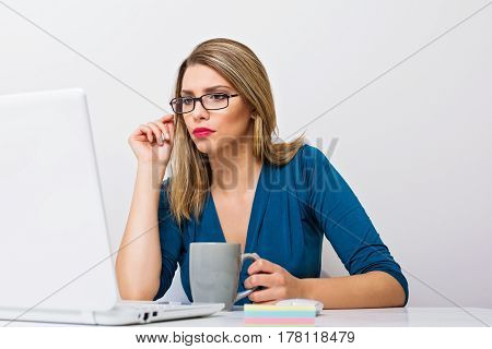 Beautiful young millennial businesswoman in eyeglasses, blue shirt and red lipstick, using laptop, reading and drinking coffee.