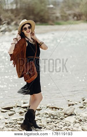 Stylish Boho Traveler Woman In Hat, Fringe Poncho Posing Near Water River Beach In Mountains, Gypsy