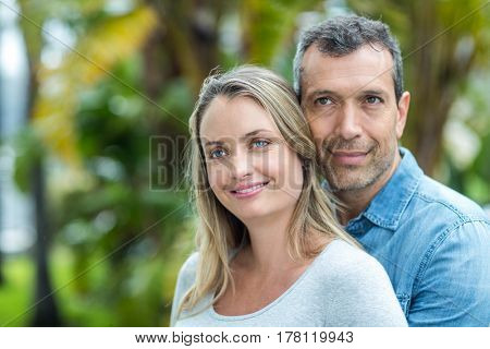 Couple looking away and smiling outdoors