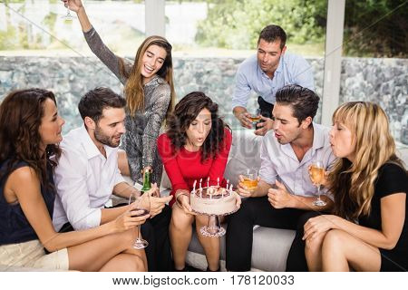 Woman blowing birthday candles with group of friends
