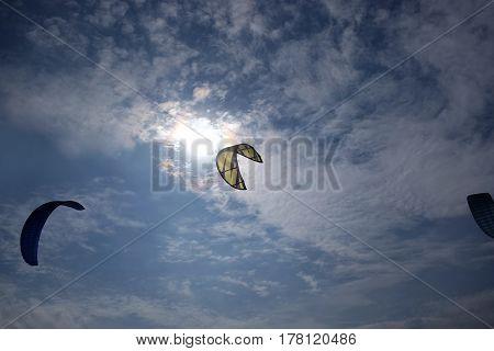 Big sport kites flying high in bright blue sky against the light