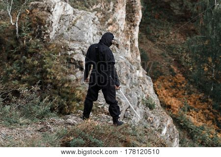 The Assassin Ninja With A Sword Is Waiting On The Cliff Rocks In Ambush