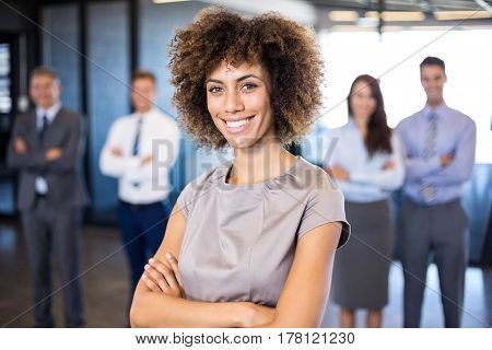 Successful businesswoman smiling at camera while his colleagues standing behind him in office