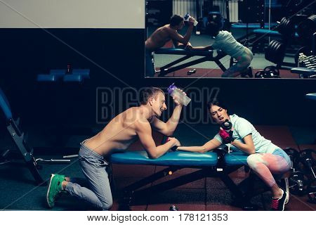 arm wrestling happy couple of pretty woman or cute girl and handsome guy or macho man with muscular torso and sexy body training in sport gym at trainer of weight lifting with water cups