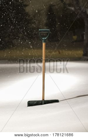 A measuring stick and a snow shovel