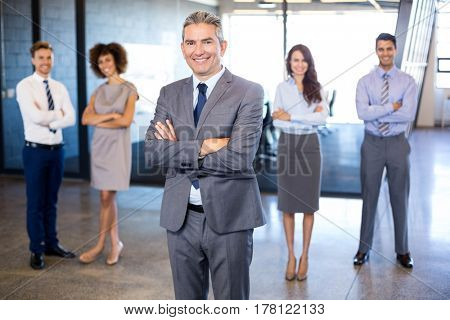 Successful businessman smiling at camera while his colleagues standing behind him in office