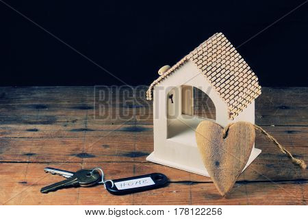 A model of a wooden house and key rings with the word
