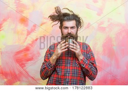 Bearded man caucasian hipster with long beard haircut and moustache holding metal mug or cup in red plaid shirt on abstract pink wall background