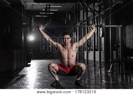 strong crossfit athlete in a heavy overhead squat lift in a cross-fit  gym.Snatch exercise.