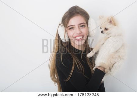 pretty girl or sexy woman with long blond hair hairstyle and happy face in black bodysuit gloves mittens earmuffs holds small cute pomeranian spitz dog or puppy pet isolated on white background