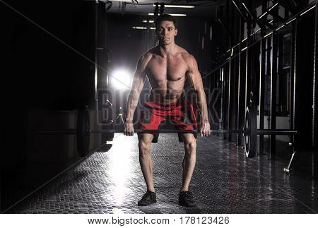 Muscular man lifting a barbell in crossfit gym.Crossfit with weights.