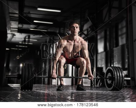 young shirtless athlete doing deadlift exercise at the gym.