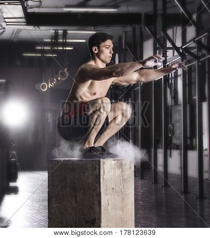Fit young man box jumping at a crossfit gym. Male athlete is performing box jumps at gym.