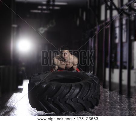Strong and fit  concentrated man pushing tire