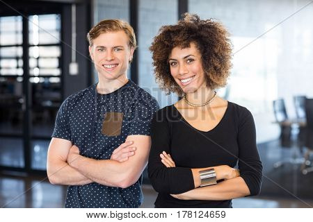 Portrait of business executives standing together with arms crossed in office