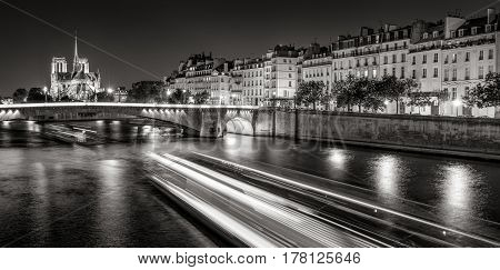 Notre Dame de Paris cathedral illuminated with Seine River and the Tournelle Bridge at night (Black & White). Ile Saint Louis Quai d'Orleans 4th Arrondissement Paris France