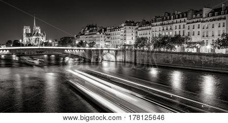 Notre Dame de Paris cathedral illuminated with Seine River and the Tournelle Bridge at night (Black & White). Ile Saint Louis Quai d'Orleans 4th Arrondissement Paris France