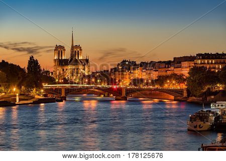 Notre Dame de Paris Cathedral Seine River and the Ile Saint Louis at twilight. Summer evening with the Sully Bridge and city lights in the 4th Arrondissement of Paris. France