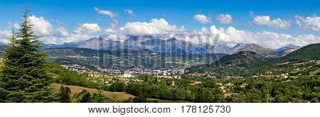 The city of Gap in the Hautes Alpes with surrounding mountains and peaks in Summer. Panoramic. Southern French Alps France