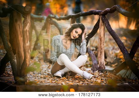 sensual girl with long legs laying down in an autumnal scene.Long legs attractive blonde with curly hair relaxing in autumnal park.Fashionable young woman posing in the forest.