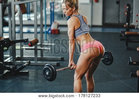 Sexy young athletics blonde girl doing deadlift with barbell. Fitness woman in pink sport clothing workout with barbell in gym