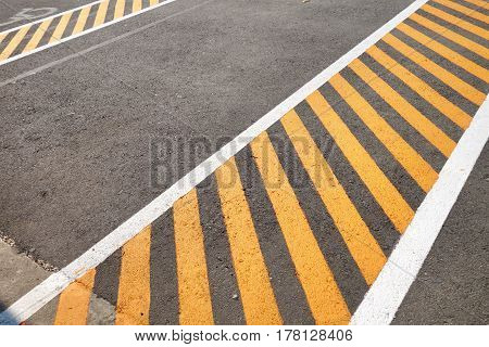 Black asphalt pavement painted with yellow stripes