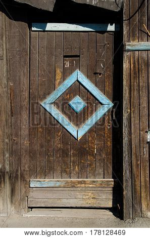 Old wooden door under the sun with wall