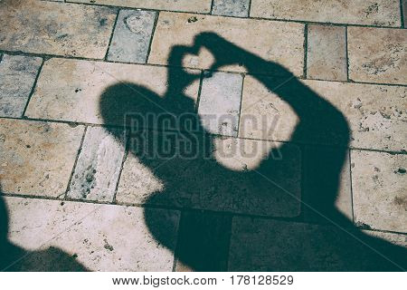 Shadow of a woman on the ground, heart texture.