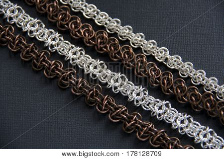 Chainmail jewelry on dark sheet of paper