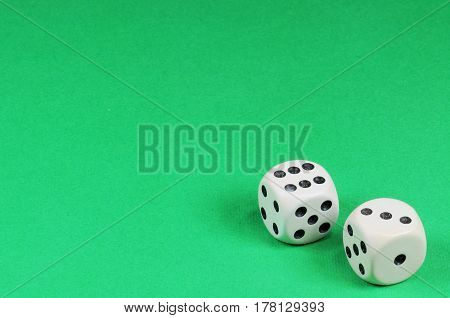 Old bone dice on green background with copy space.