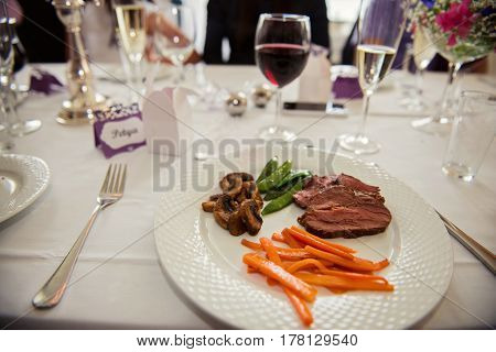 Main course menu with beef, carrots, beans and mushrooms freshly served on a white plate. Main course for Hotel, restaurant or pension.