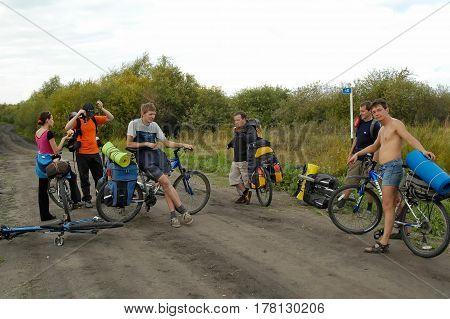 Tyumen, Russia - September 10, 2006: Group of bicycle tourists stopped for rest on unpaved road
