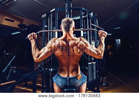 Strong Bodybuilder Doing Heavy Weight Exercise For Back On Machine. Smoke on background