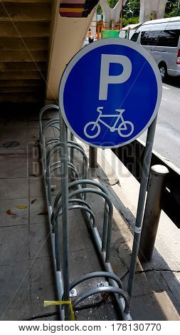 Empty outdoor bike parking with bicycle sign on brick wall