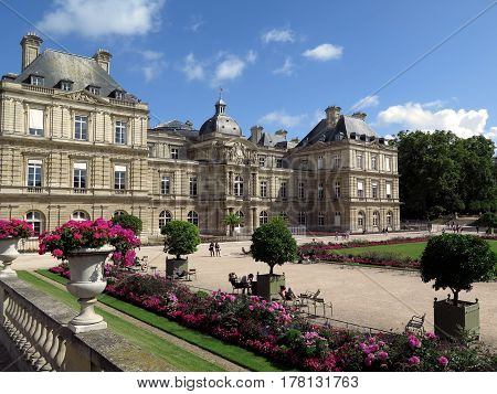 Inside view of the Luxembourg garden in Paris, France, with the Palais of the Luxembourg in the background. Photo taken in the morning in summer. Some tourists and Parisians take the sun sitting on chairs.