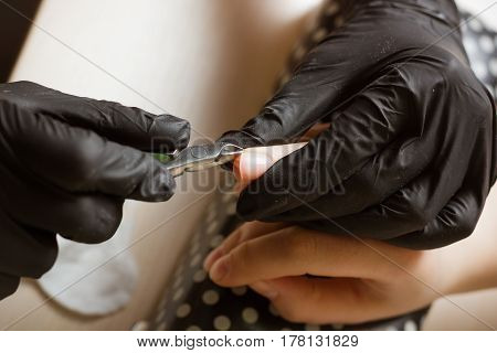 Top view manicurist polishing index finger for manicure in nail beauty salon. Step of manicure process.