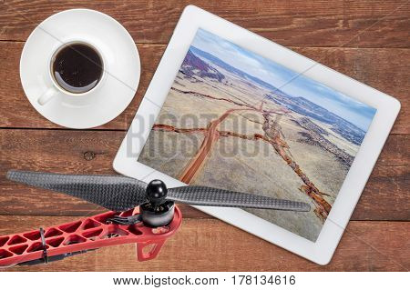 aerial photography concept - reviewing pictures of Colorado foothills on a digital tablet with a drone rotor and coffee, screen picture copyright by the photographer