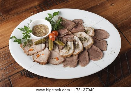 Baked roast beef, chicken rolls, tongue and pork meat with vegetables in a white oval plate. Cold appetizer with sauce. Wooden background.