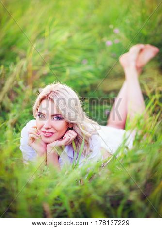 Smiling beautiful young woman lying among the green grass