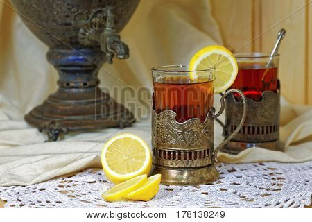 Russian samovar, tea with lemon in faceted glasses with cup holders. Tinted photo in vintage style.