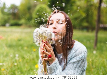 Pretty girl blowing dandelion in summer park. Green grass and beautiful nature