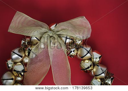 A golden festive bell wreath with a bow