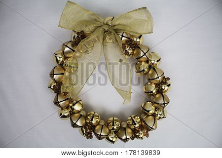 A full round golden bell wreath with bow on a white background